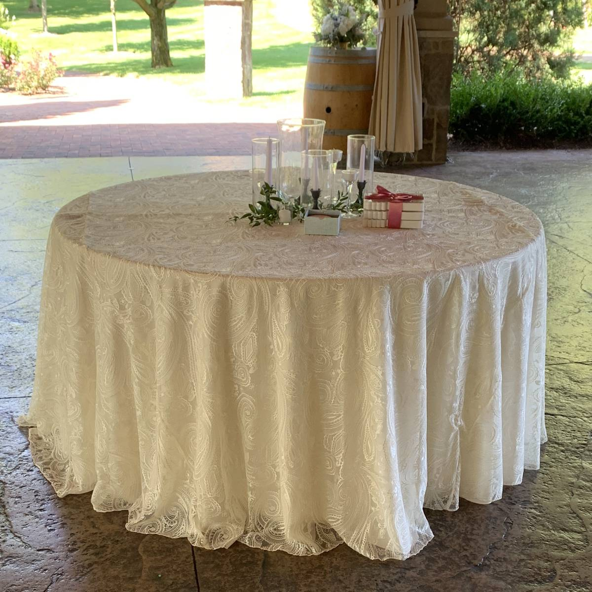 "108"" Round Ivory Solid Tablecover With 108"" Round Ivory Paisley Lace Tablecover On 48"" Round Wood Topped Table"