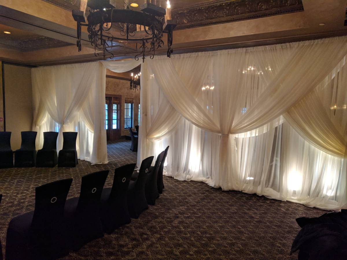 Sheer Ivory Backdrop With Sheer Ivory Front Layer Crisscrossed Tied With Uplights