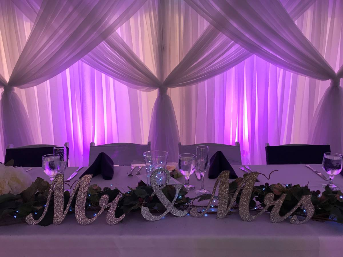 Sheer White Backdrop With Sheer White Front Layer Crisscrossed Tied With Colored Uplights